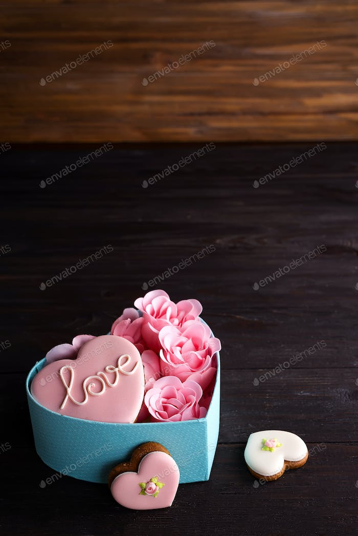 Hearts cookies in box. Festive round blue box with cookies and Rose on dark wooden background, copy