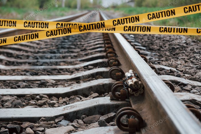 Be aware. Dangerous explosive lying on the railway. Yellow caution tape in front