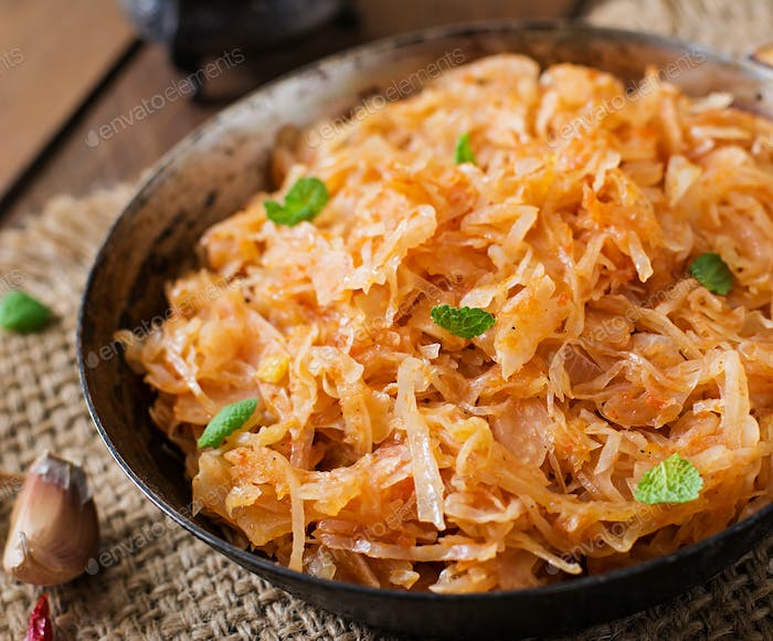 Stewed cabbage on the old wooden background in rustic style