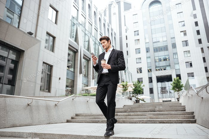 Businessman using cell phone and drinking coffee in the city