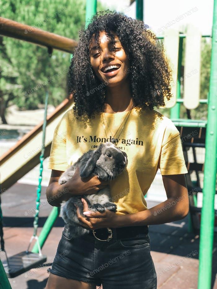 schwarz Frau halten ein niedlich Häschen