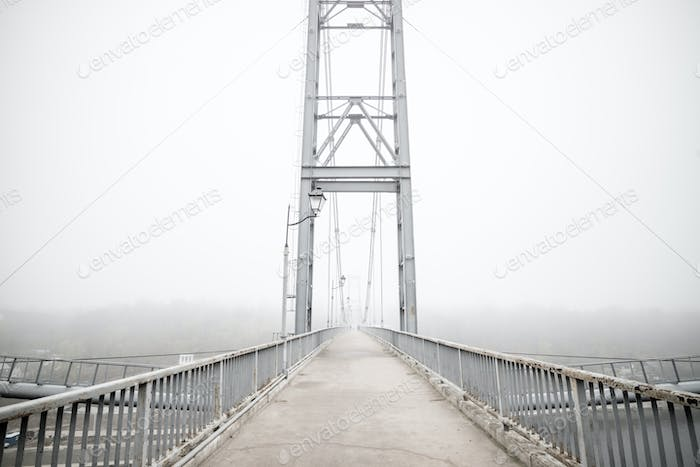 Bridge with fog in grey tones. Melancholy misty landscape with bridge and lamps