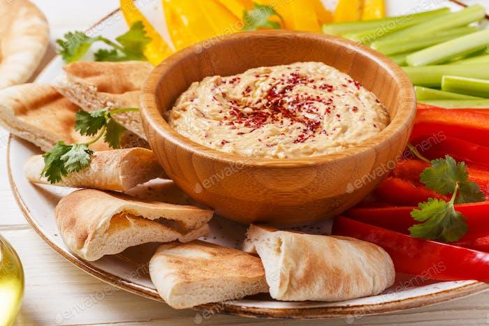 Hausgemachter Hummus mit verschiedenen frischen Gemüsesorten und Pitabrot.