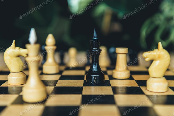 Closeup view of black and white chess figures on chess board. Selective focus on black bishop