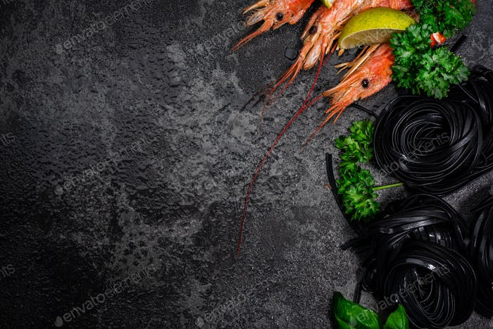 Squid Ink Black Pasta Spaghetti with Seafood and Fresh Herbs. Border Background with Copy Space.