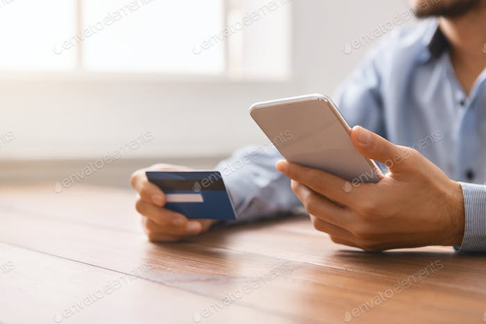 Man using credit card and smartphone for shopping online