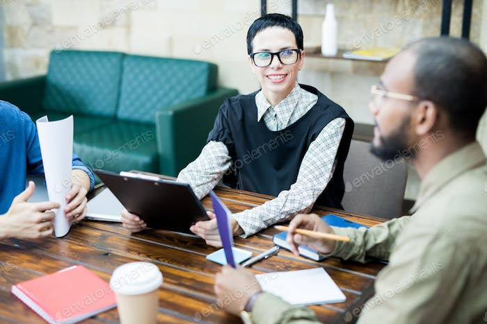 Confident female creative specialist talking to colleagues
