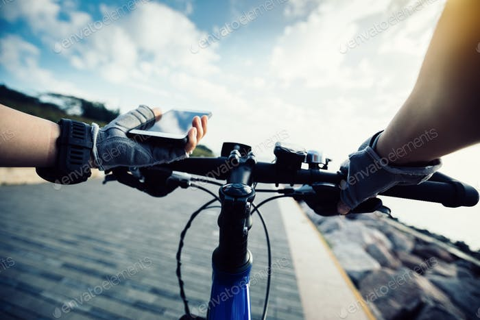 Cyclist hands use mobile phone