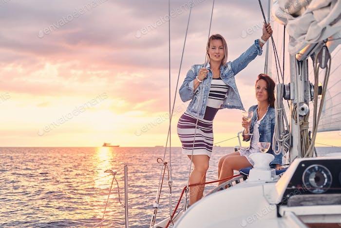 Weibliche Freunde entspannen auf der Yacht während des Sonnenuntergangs auf hoher See.