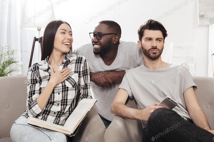 Junge Freunde sitzen auf dem Sofa fröhlich diskutieren etwas