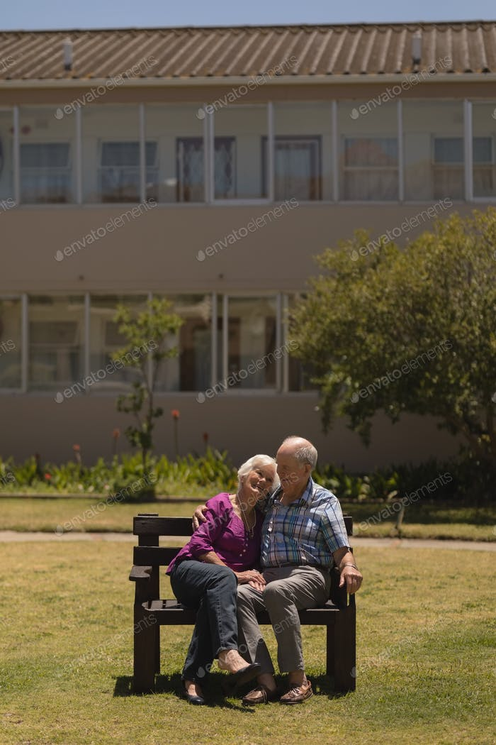 Front view of active senior couple sitting together and doing cuddle on the bench in the park