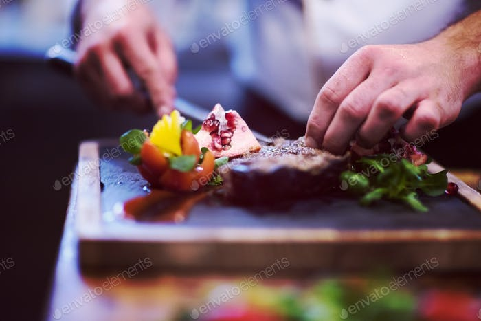 closeup of Chef hands serving beef steak