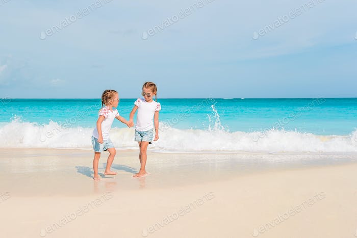 Adorable little girls have a lot of fun on the beach
