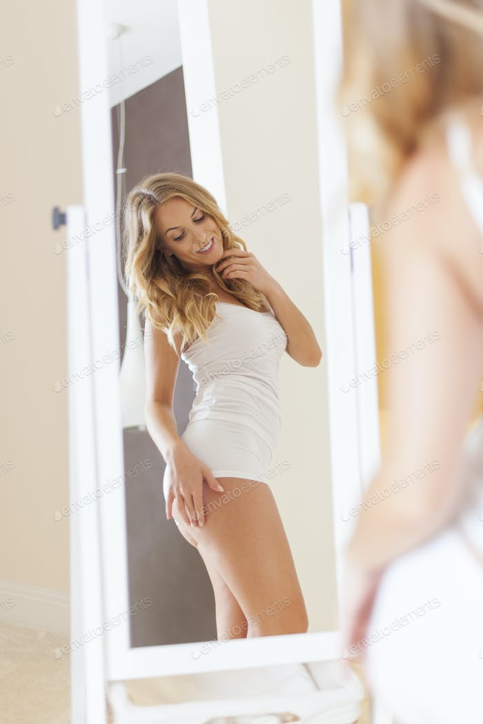 Blonde woman standing in front of mirror and checking her body