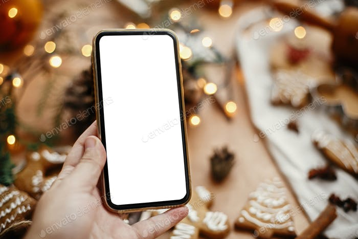 Phone with empty screen in hand on background of christmas lights