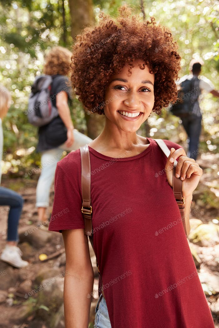Smiling millennial African American woman hiking in a forest, waist up, close up, vertical