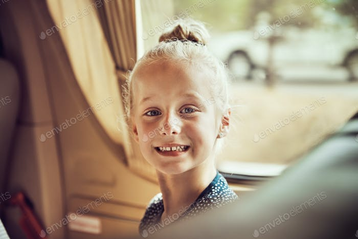 Cute little girl smiling while sitting in a car