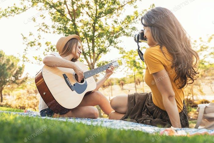 Beautiful women having fun playing guitar and photo camera in the park.