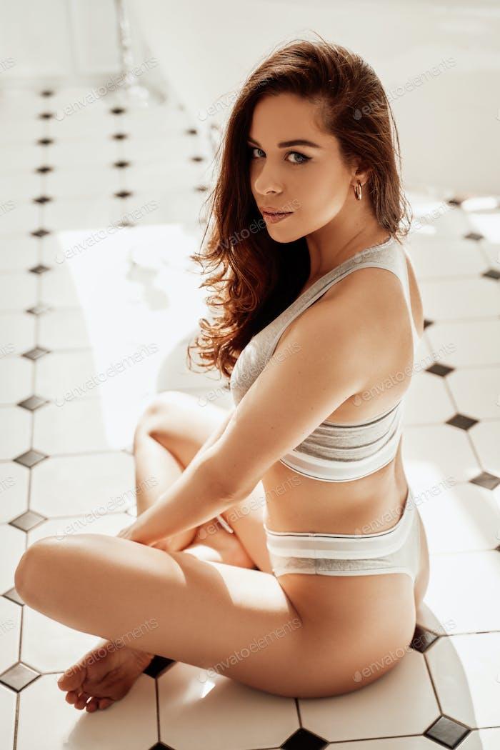 Junge Brünette Frau posiert auf einem Badezimmer Fliesenboden und trägt sportive graue Dessous