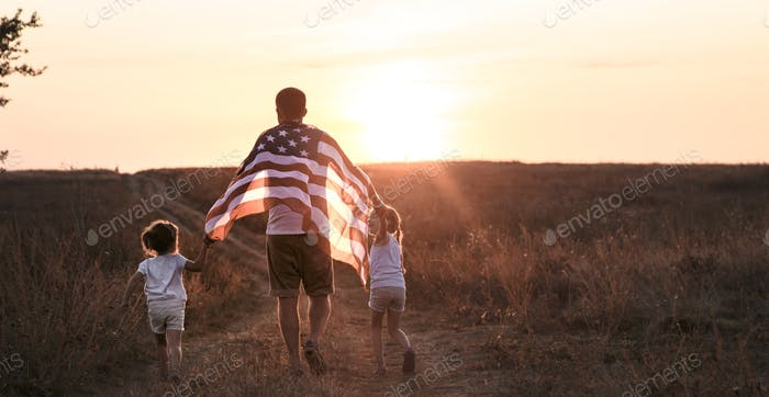 A happy family with an American flag at sunset.