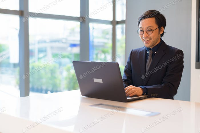 Happy Asian businessman using laptop at the office by the window