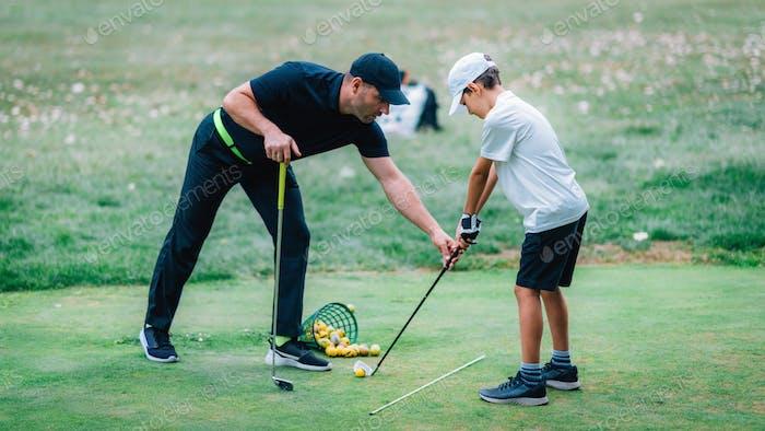 Golfunterricht. Ein Golf-Instruktor und ein Junge üben auf einem Golf Übungsbereich