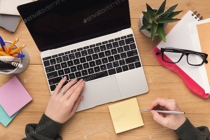Woman typing on laptop computer and writing notes