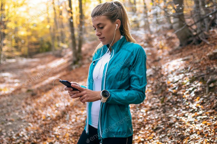 young woman listening to music while relaxing after running in the forest in the autumn morning