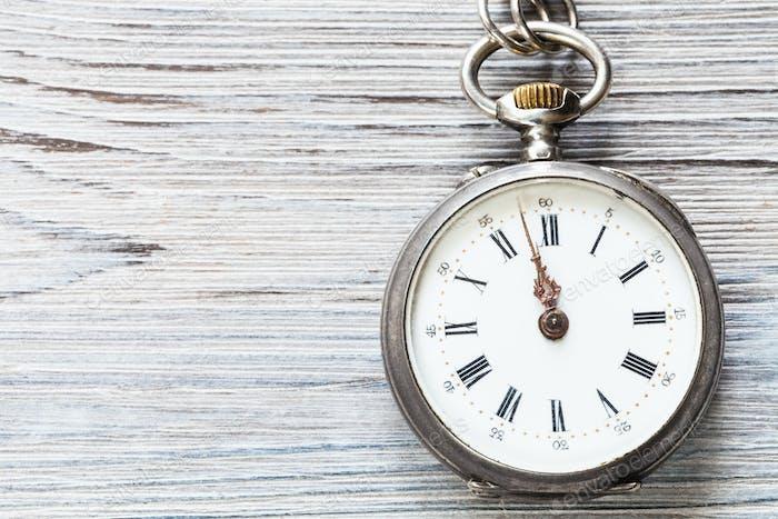 zwei Minuten bis zwölf auf Retro-Uhr auf grauem Holz