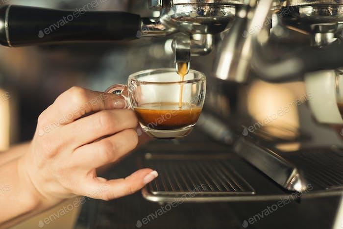 Closeup of barmen hand brewing espresso in professional coffee machine
