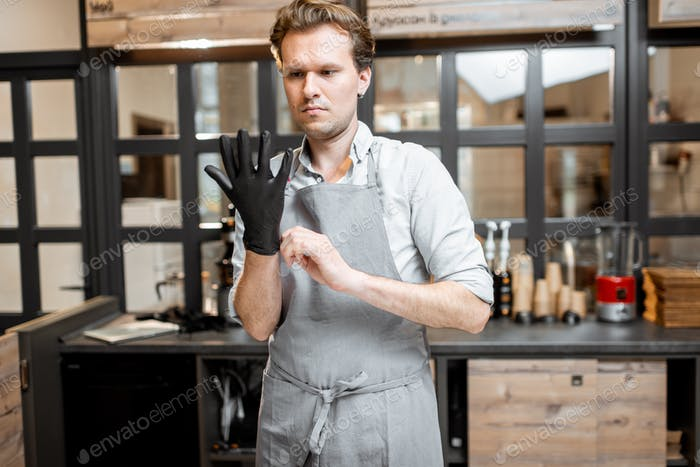 Salesman wearing gloves in the cafe