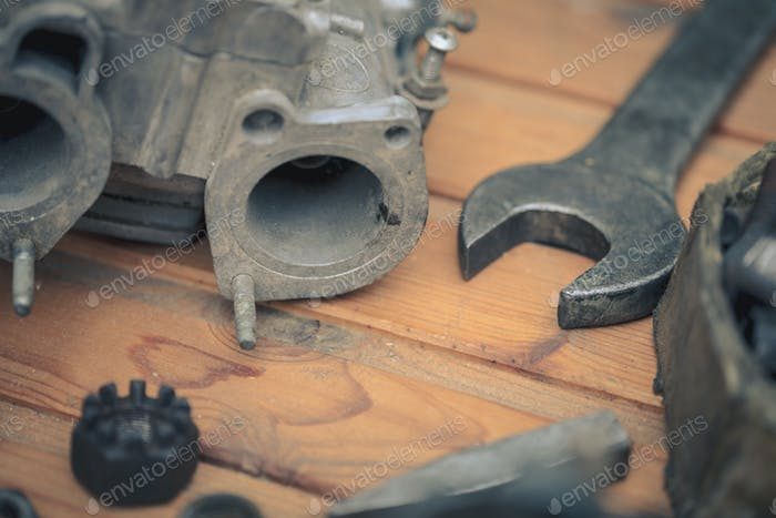 Carburetors for a car engine with tools on wooden table