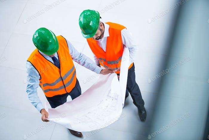 Architects checking blueprint