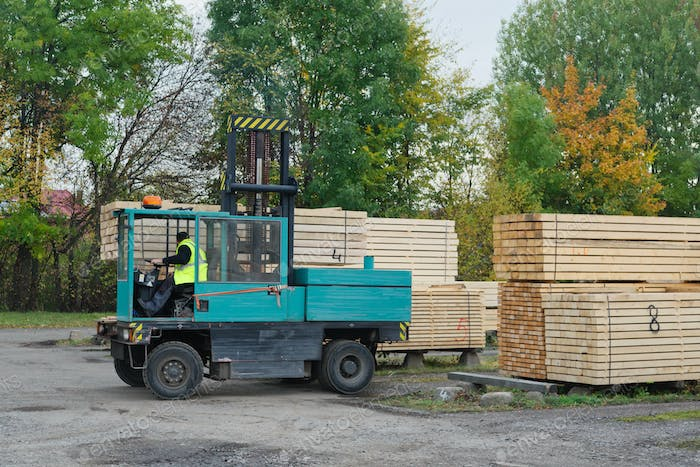 Forklift transports the boards at the plant for woodworking