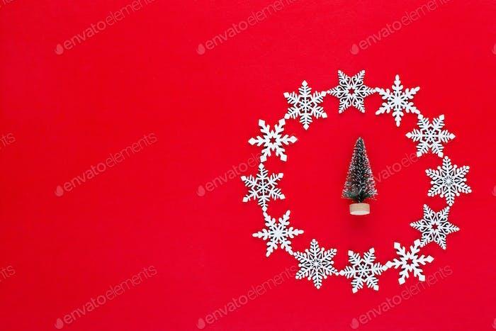 Weihnachtskomposition. Weiße Schneeflocken Kranz Dekorationen auf rotem Hintergrund.