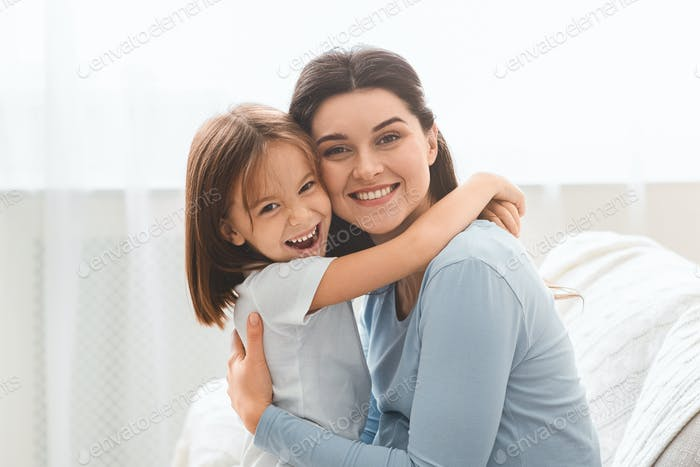 Happy family portrait of embracing mother and little daughter