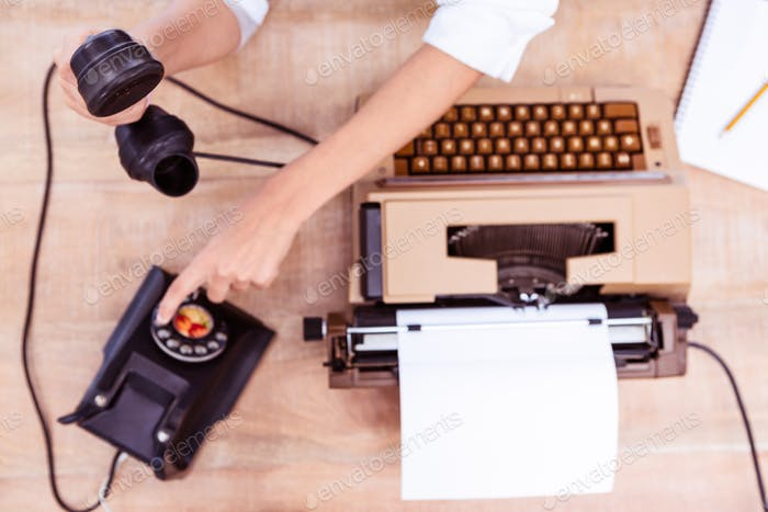 Above view of typewriter and old phone on wooden desk