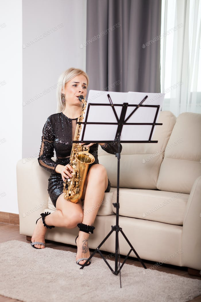 Gorgeous saxophonist girl playing at her musical instrument in t