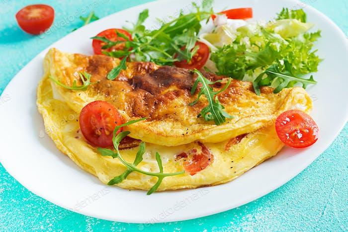 Omelette mit Tomaten, Käse und Rucola auf weißem Teller.