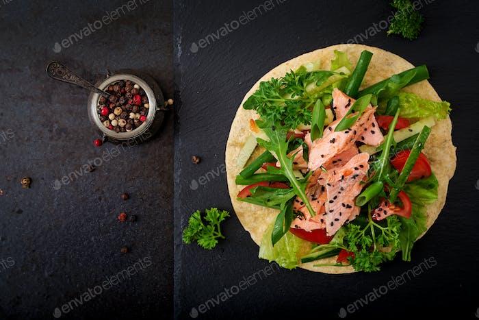 Gesunde mexikanische Mais-Tacos mit gebackenem Lachs, Salat, Tomaten, Gurken und Rucola.