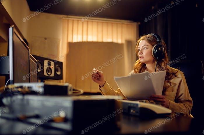 Female engineer in headphones, recording studio