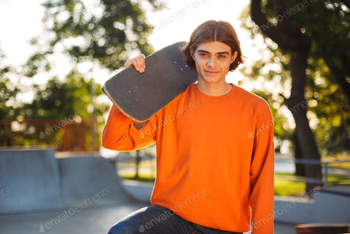 Young smiling skater in orange pullover happily looking in camer