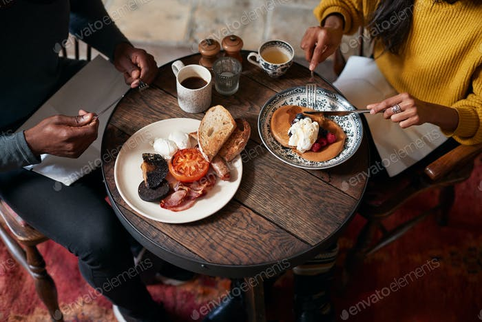 Close Up Of Couple At Table In Traditional English Pub Eating Breakfast
