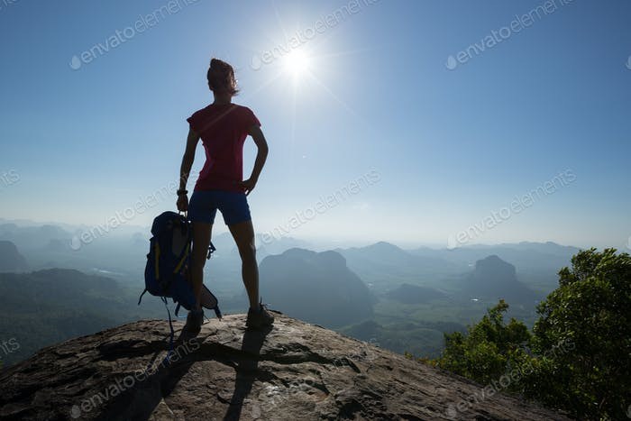 Successful hiker in the sunrise mountain top