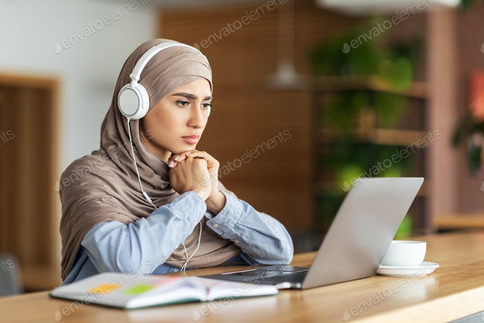 Girl in headscarf having online lesson on laptop at cafe