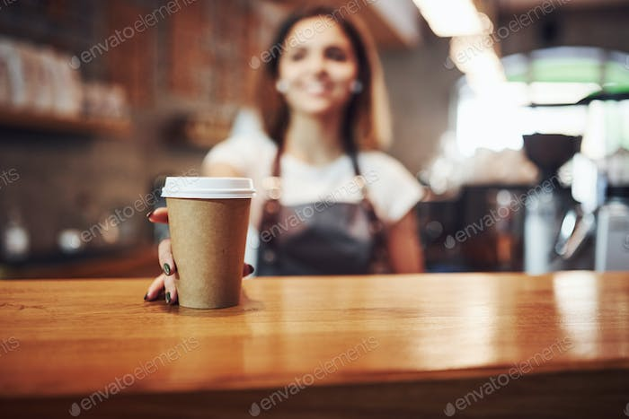 Buying drink. Young female employee indoors. Conception of business and service