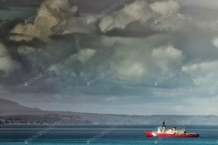 Coastguard boat sailing along coastline under moody sky.