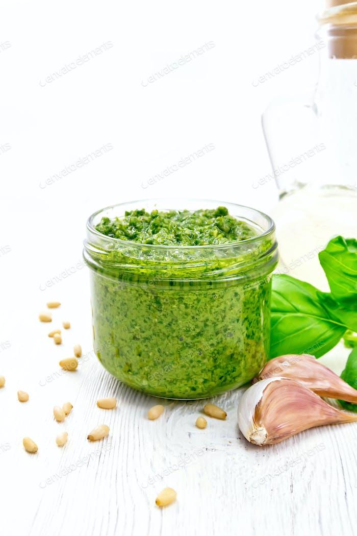 Pesto in glass jar on white board