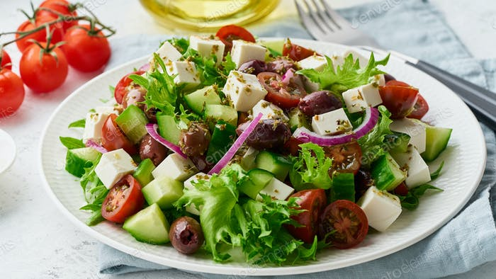 Greek Salad with feta and tomatoes, dieting food on white background closeup