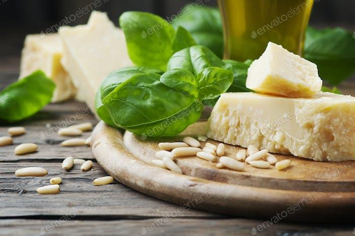 Basilikum, Käse, Kiefer und Olivenöl auf dem Holztisch